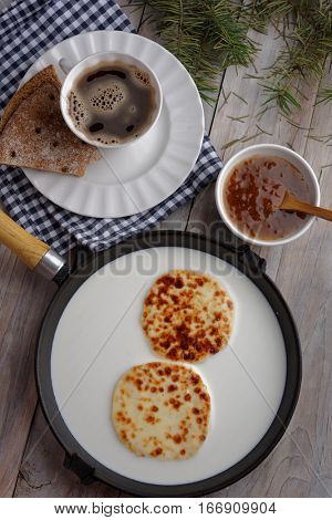 Swedish breakfast with mini farmer cheeses in an iron cooking pan, cloudberry jam, and a cup of coffee