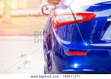 Luxury car. Back body reflections. The back of a blue luxury car. Reflections and lights on the glazed body of the car. Headlights, position indicator and lights.