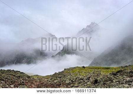 Mountain peaks shrouded cold mist. Eastern Sayan. Siberia. Russia