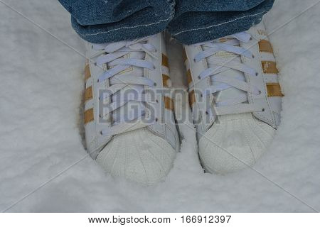 Closeup of white sneakers woman's stomp on the ground covered with snow at Kyoto, Japan