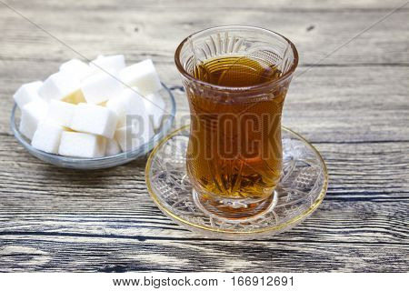 Turkish tea. Crystal glass Turkish tea, a plate of sugar on a wooden table. Can be used as a photo for a menu of Eastern confectionery, cafe.