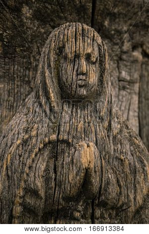 Virgin Mary carved on ancient wooden icon. The wooden figure of the Virgin Mary. Old wooden icon of the Virgin Mary with a close-up. Portrait of the Virgin Mary carved from wood. Cracked figurine.