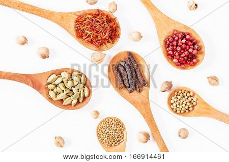 various spices and herbs in wooden spoon on white background.