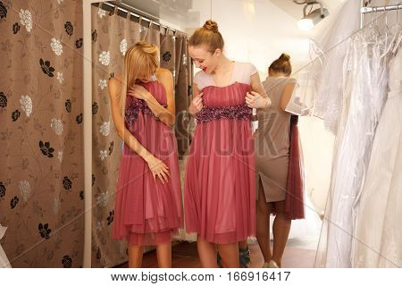Two girlfriends - bridesmaids- having fun - looking for dresses for wedding