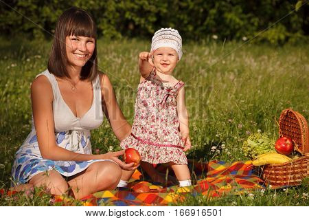Young woman with her little 1 year old daughter is having picnic in the park