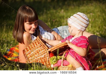 Young beautiful woman with her little 1 year old daughter having fun on the picnic