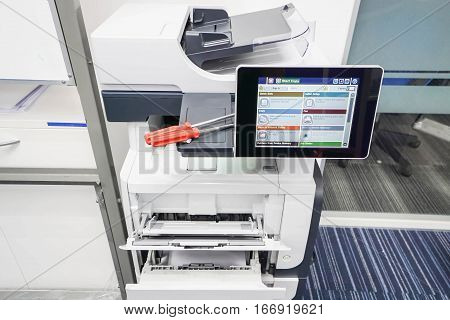 two red screwdrivers on printer for repair assistance