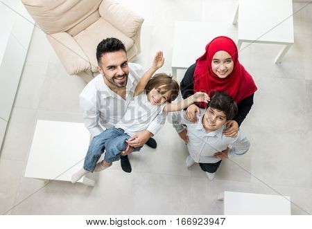 Happy Arabic Muslim family at modern home having fun and good time together