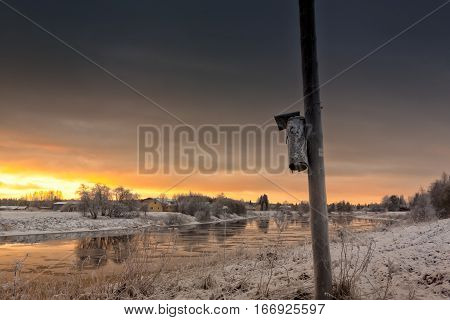 An old birdhouse attached to the telephone pole against the sunrise in the Northern Finland. The winter sun rises over the river.