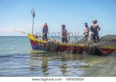 Labuan,Malaysia-Aug 29,2015:Fisherman on the boat with fishing net at Labuan island.Fishing industry  is one of the occupations of local people in Labuan island.