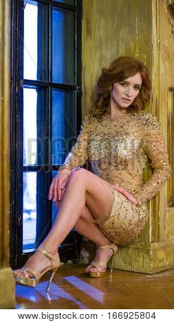 Woman in a short shiny dress with sequins sitting in the doorway in the old hall with golden walls