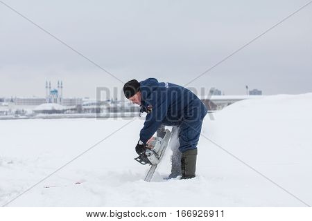 KAZAN, RUSSIA - JANUARY 19, 2017: russian MoE lifeguard cuts ice with a chainsaw - rescuer on ice at winter day during Christ's baptism holiday, telephoto