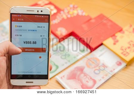 ZhongshanChina-Jan 262017:preparing a mobile red pocket on WeChat for Chinese new year 2017 with some real ones on background.January 28 is the 1st day of year Rooster & sending receiving red pockets is a traditional culture.