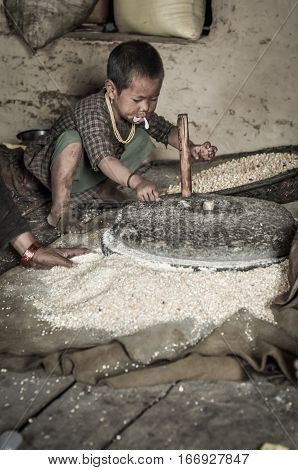 Child With Stone Grain Mill In Nepal