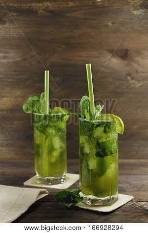 A photo of mojito cocktails with mint leaves, wedges of lime, and drinking straws, on a dark wooden background with copyspace. Selective focus