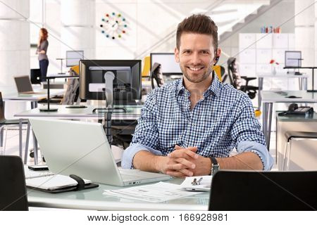 Happy casual successful caucasian business consultant at startup office, sitting at table with laptop computer, smiling, confident, looking at camera,