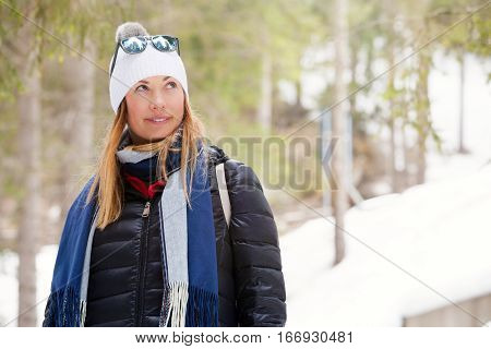 Woman smiling with winter clothing. Snow and nature, mountains vacation. Coat down jacket, wool hat and scarf. In the mountains with snow and trees.