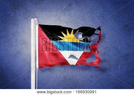 Torn flag of Antigua and Barbuda flying against grunge background