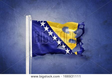 Torn flag of Bosnia and Herzegovina flying against grunge background