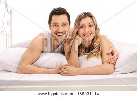 Happy couple lying in bed and looking at the camera isolated on white background