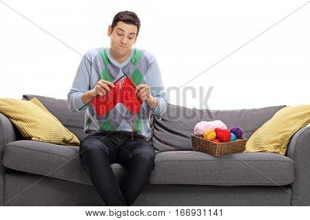 Confused guy sitting on a sofa and attempting to knit isolated on white background