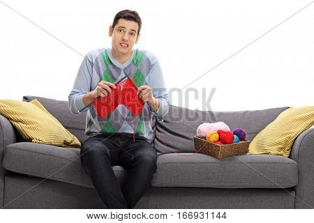 Confused young man attempting to knit and looking at the camera isolated on white background