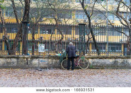 Old Man With His Old Bike On Hanoi Street In Winter Season