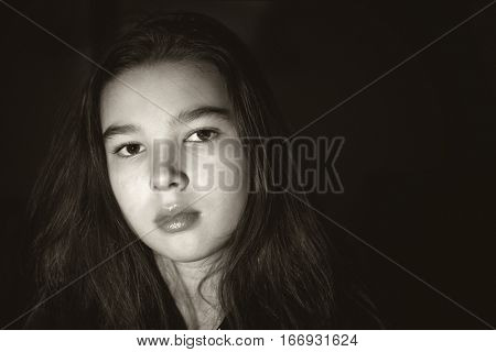 Sad teen girl portrait on black background. Low-key style. Black and white photo