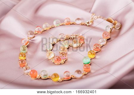 Necklace and bracelet with colorful stones on pink silk background.
