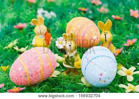 Easter bunny and egg candles on artificial grass background.
