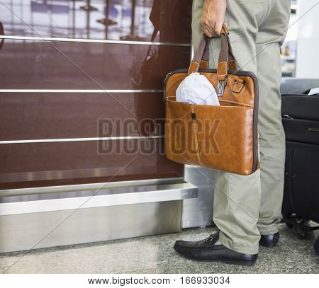 Man Hand Holds Leather Bag Standing In Front Of Airport Check-in Desk. Concept Of Tourism Via Aviati