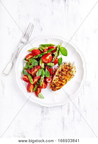Grilled chicken breast with asparagus and cherry tomato salad