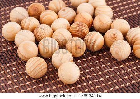 Many wooden balls on brown bamboo background.