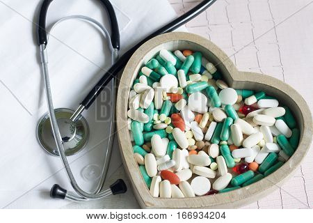 Stethoscope and pills in heart against cardiogram medical concept