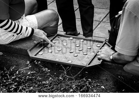 close up hand of old asian Thai man play street hourse board game on street