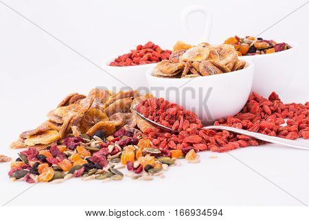 Dried fruits berries and seeds in bowls on gray background.
