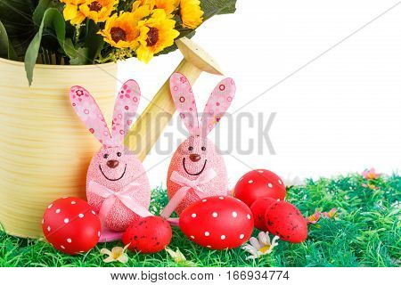 Easter decoration with bunnies eggs and flowers in watering can on artificial grass.