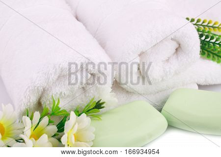 White rolled towels with soaps and flowers closeup picture.