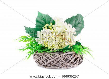 Fabric flowers in wicker basket isolated on white background.