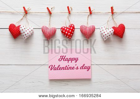 Valentine background with greeting card and diy sewed pillow hearts row border on red clothespins at rustic white wood planks. Happy lovers day card mockup, copy space