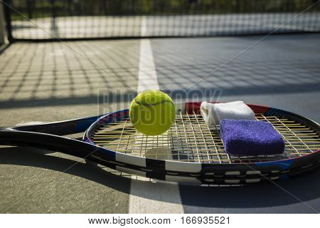Tennis Ball, Racket, Wristbands On Tennis Court