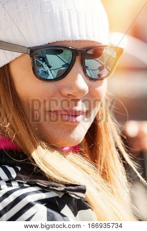 Beautiful cheerful woman with winter clothing. Season and winter day in the mountains. The woman wearing woolen cap and sunglasses.