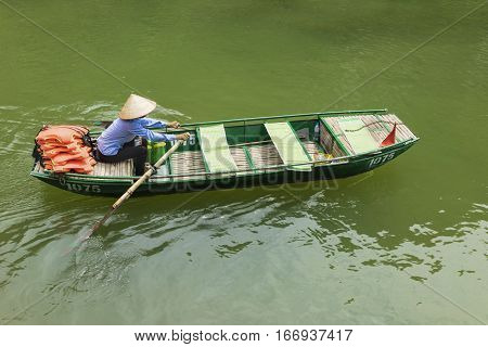 Vietnamese woman rowing boat on river in Ninh Binh