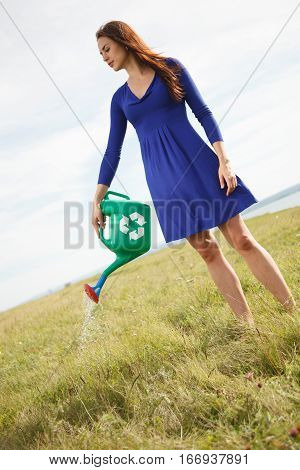 Woman outdoors holding green watering pot with recycling sign and watering ground