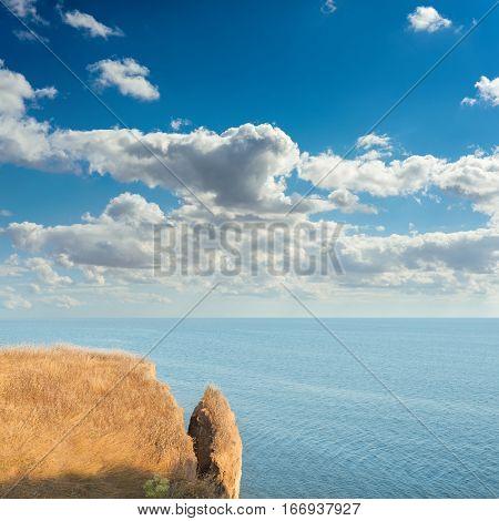 precipice over sea and clouds in blue sky