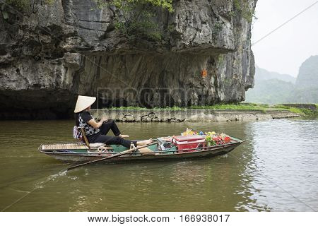 Vietnamese Woman In Traditional Conical Hat Rows Boat Into Natural Cave On Ngo Dong River, Tam Coc,