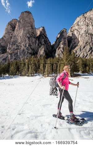 Snowshoes, active smiling woman in the snow. Winter sports. Hiking in the snow. Snowshoes at the foot of a smiling young woman on vacation. sunglasses and winter ski clothing.