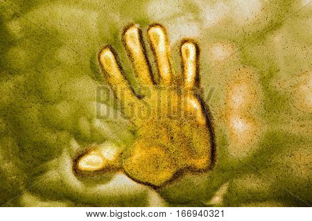 Hand print in a sand and light table. Sence of danger concept.