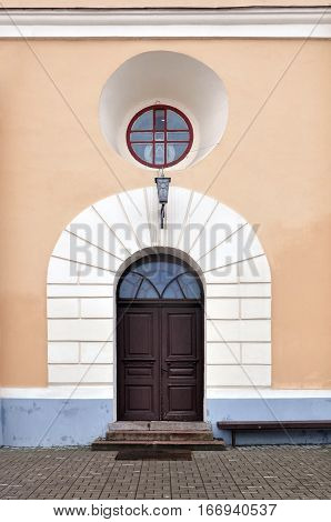 Arched wooden doorway with white decorative elements and round window with stained glass. Entrance to the Bernardine Church in Grodno, Belarus.