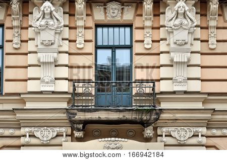 Facade of old building with sculptures of women in Art Nouveau style (Jugendstil) and balcony. Riga, Latvia.